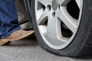 Motorist Kicking Flat Tyre On Car